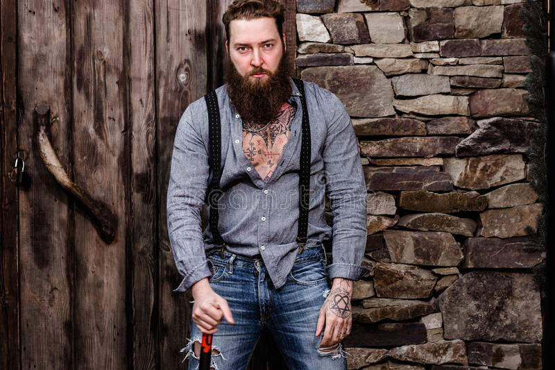 有胡子的残酷在在背景的时髦的便服立场穿戴的他的手上的坚强男人和纹身花刺  库存照片