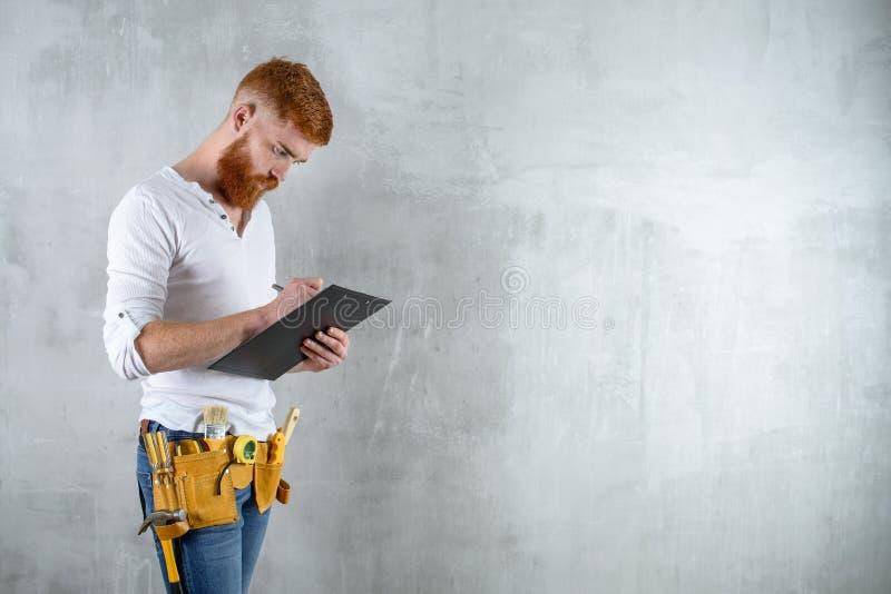 有胡子的残酷建筑师,工程师在片剂写 免版税图库摄影