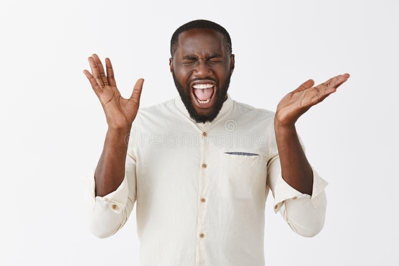 有胡子的激动的感情非裔美国人的人在白色衬衣大声尖叫从幸福和触目惊心 免版税库存图片