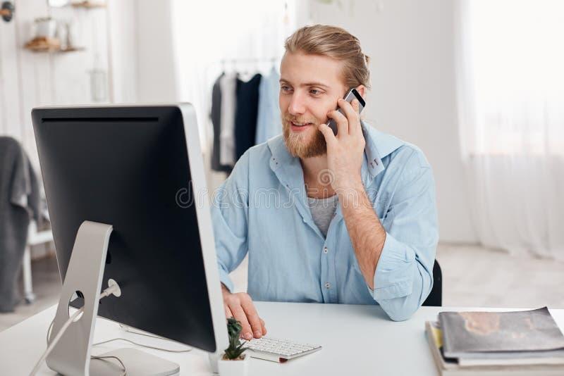 有胡子的熟练的年轻金发撰稿人在新的文章,在键盘的类型工作,有电话交谈,谈论 免版税库存照片