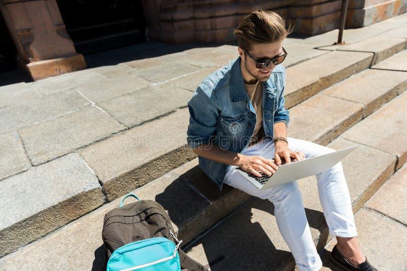 有胡子的爽快年轻的人使用在街道上的小配件 免版税库存图片