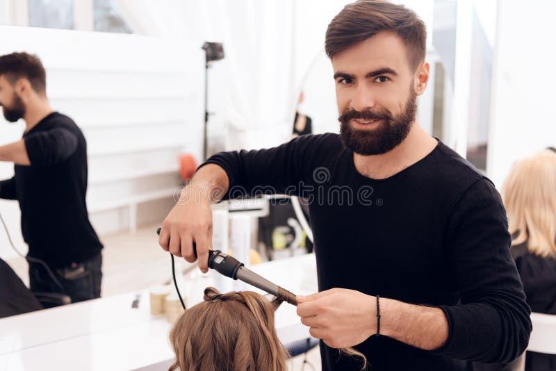有胡子的理发师在美丽的小女孩的头发做卷毛有卷发夹的 库存图片