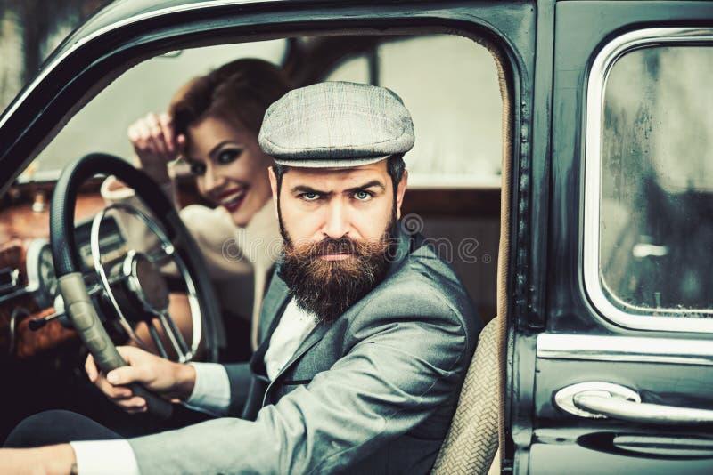 有胡子的男人和性感的妇女汽车的 有胡子的人司机在与性感女孩的日期减速火箭的汽车的 免版税库存图片