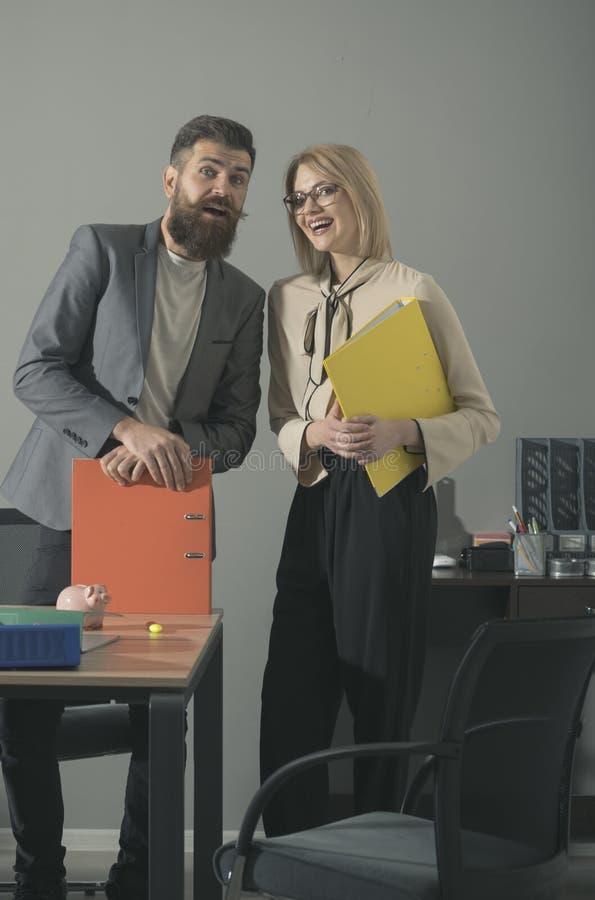 有胡子的男人和肉欲的妇女微笑与黏合剂的,文书工作 愉快的同事在现代办公室 企业夫妇微笑 免版税库存照片