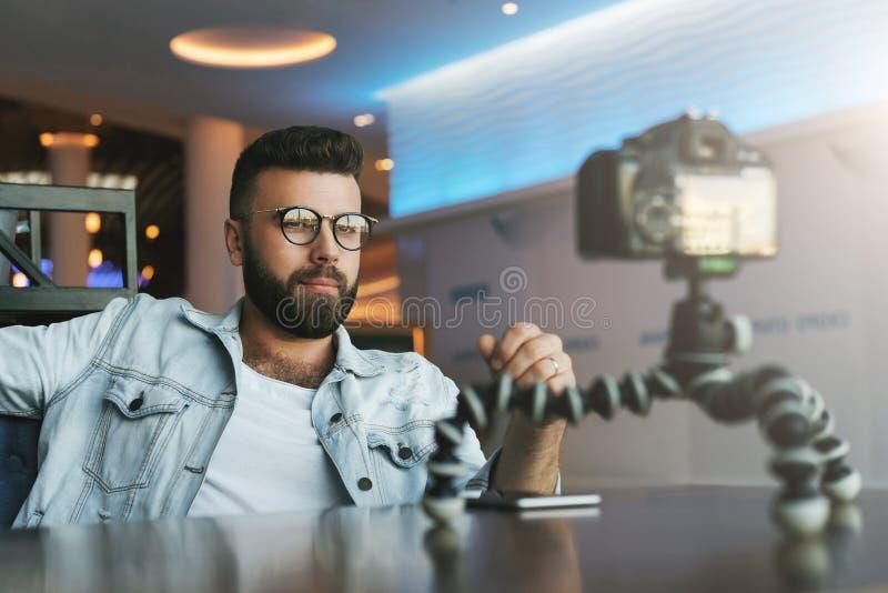 有胡子的男性录影博客作者创造他的渠道的录影内容 人vlogger在与三脚架的照相机解除自己 库存照片