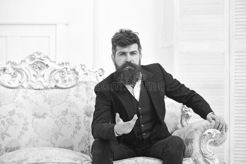 有胡子的穿着经典衣服的人和髭,坐古板的扶手椅子或沙发 报告人,明智的讲师概念 库存照片