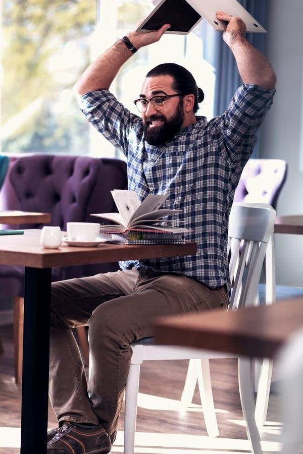 有胡子的自由职业者感觉疯狂和恼怒在出故障他的任务以后 库存照片