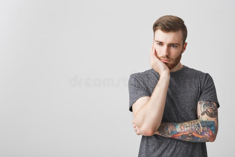 有胡子的英俊的人和被刺字的武器储备头画象有时髦的发型的用看在旁边与疲乏的手 图库摄影