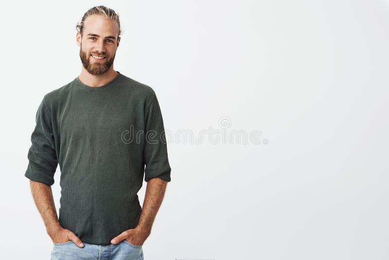 有胡子的英俊的北欧人和在灰色衬衣和牛仔裤微笑的时髦的发型,看在照相机,保留手  库存照片