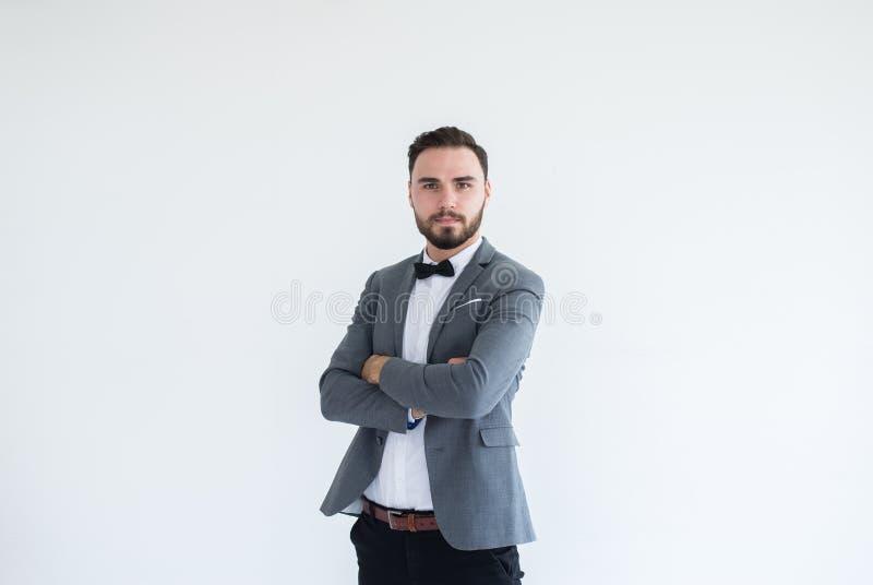 有胡子的英俊的白种人人在正式无尾礼服和衣服身分和在白色背景的发怒胳膊,复制文本和二的空间 库存图片