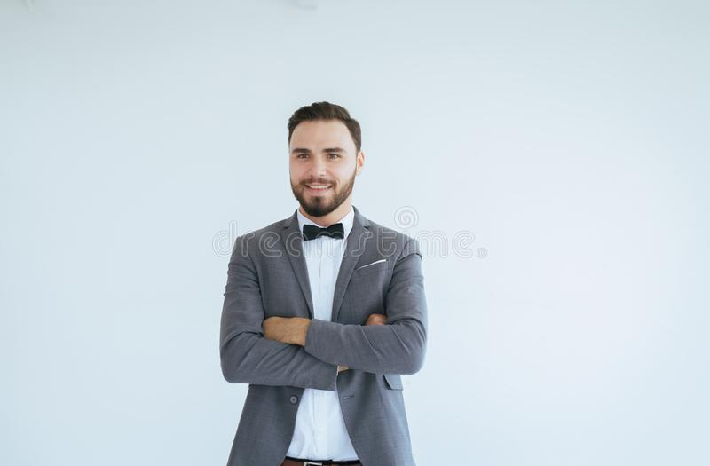 有胡子的英俊的白种人人在正式无尾礼服和衣服身分和在白色背景的发怒胳膊,复制文本和二的空间 免版税库存照片