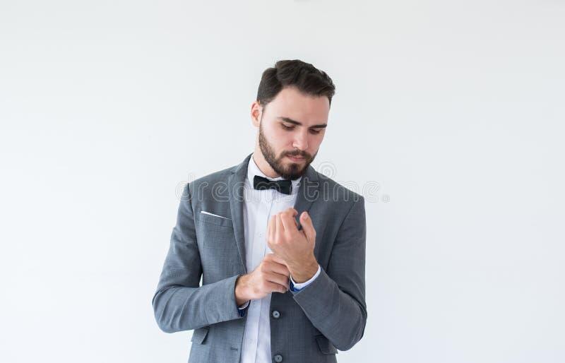 有胡子的英俊的白种人人在正式无尾礼服和衣服身分和装饰在白色背景,复制文本和二的空间 免版税库存照片