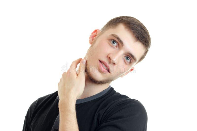 有胡子的英俊的年轻人掀动了他的头并且在脖子附近保留手在白色背景 库存图片