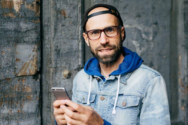 有胡子的蓝眼睛的人特写镜头画象拿着手机的时髦的盖帽和牛仔布滑雪衫的浏览cheking他的e的互联网 库存照片