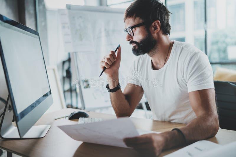 有胡子的行家专业佩带的眼睛玻璃工作在有台式计算机的现代顶楼演播室办公室 空白白色 免版税图库摄影