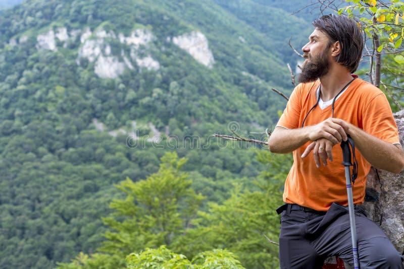 有胡子的年轻远足者敬佩看法的从登上的顶端 库存照片
