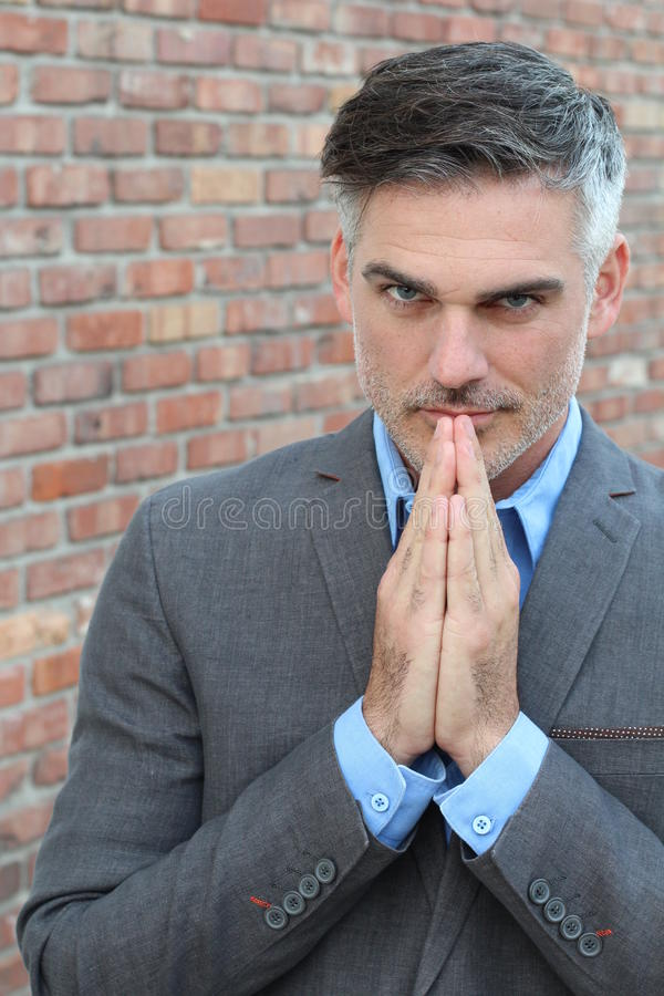 有胡子祈祷的英俊的成熟人 免版税库存图片
