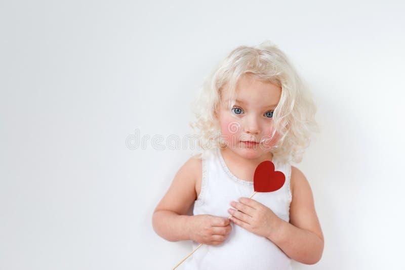 有胭脂面颊的美丽的严肃的蓝眼睛的小孩子,穿戴随便,有白肤金发的卷发,拿着棍子以形式 免版税库存图片