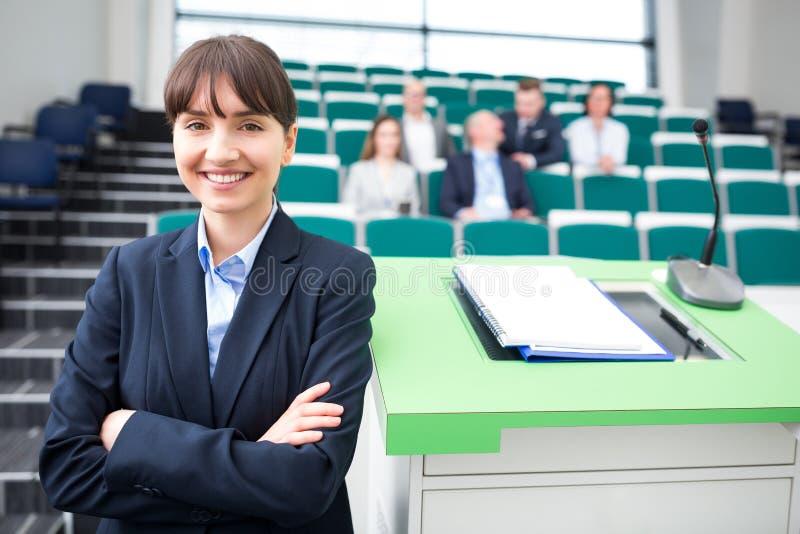 有胳膊横渡的微笑的女实业家在教室 免版税库存图片