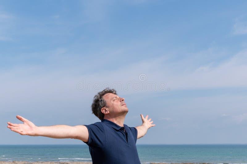 有胳膊的人在海的天空中有大蓝色拷贝空间天空的 库存照片