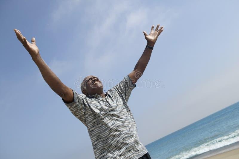 有胳膊的人被伸出在海滩 图库摄影