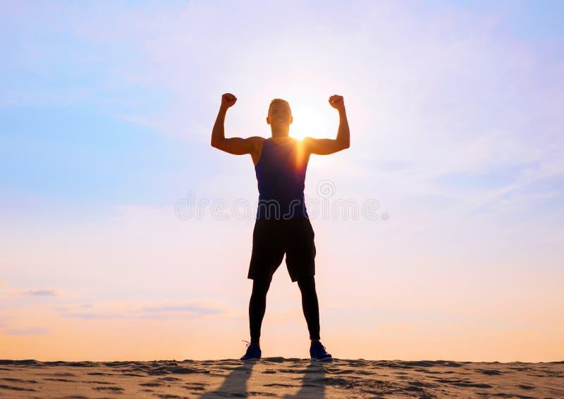 有胳膊的健身男性运动员庆祝成功和目标 免版税库存照片