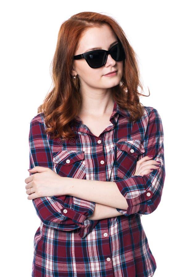 有胳膊的女孩在格子花呢上衣横渡了 免版税图库摄影