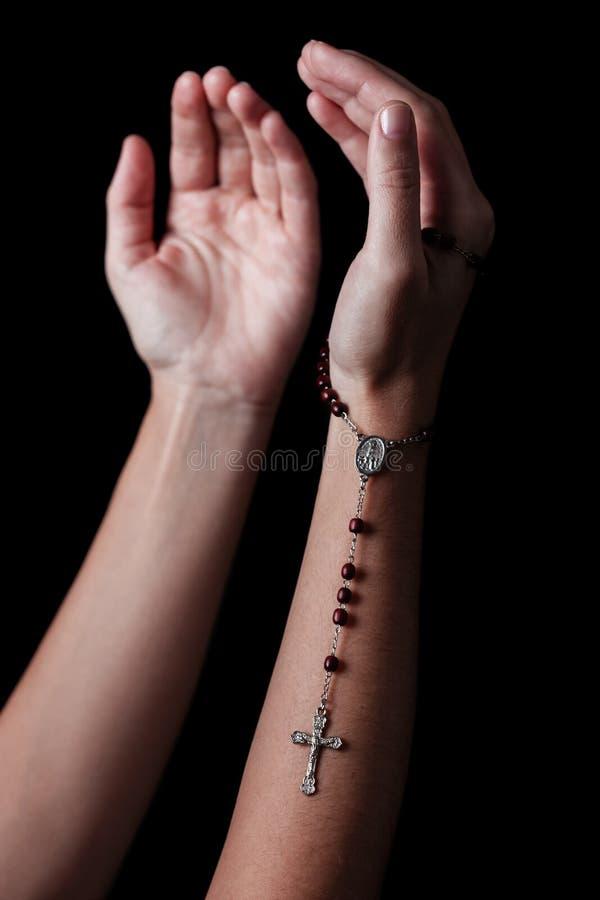 有胳膊的女性手伸出祈祷和拿着有十字架或耶稣受难象的念珠 免版税库存图片