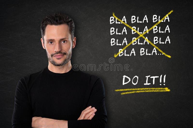 有胳膊的年轻可爱的白人横渡了与'bla bla bla 它'在黑板背景的文本 免版税库存图片
