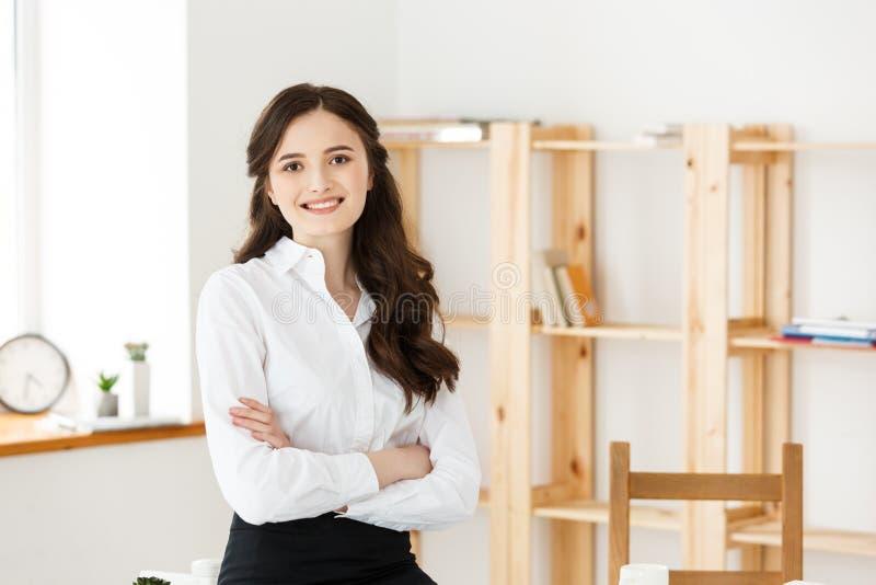 有胳膊的微笑的成熟专业女实业家在办公室横渡了坐书桌 免版税库存图片