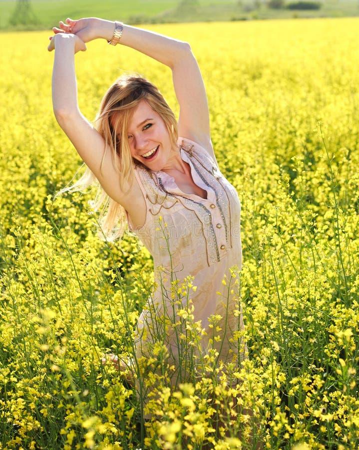 有胳膊的愉快的女孩,放松在春天黄色领域 免版税库存图片