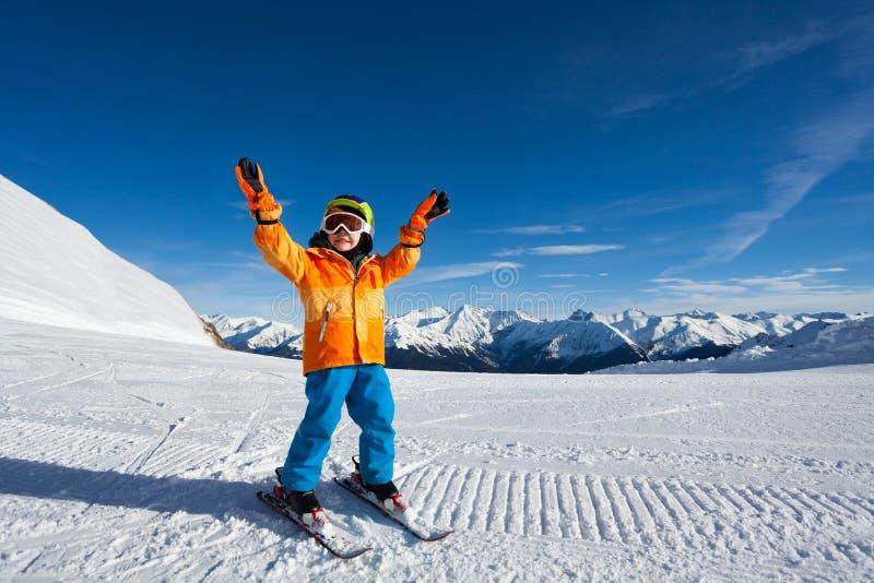 有胳膊的愉快的男孩上升和在滑雪轨道的滑雪帽 库存照片