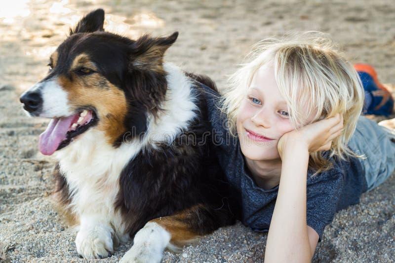 有胳膊的愉快的男孩在爱犬附近 库存图片