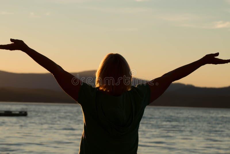 有胳膊的成熟妇女被伸出在日落 库存照片