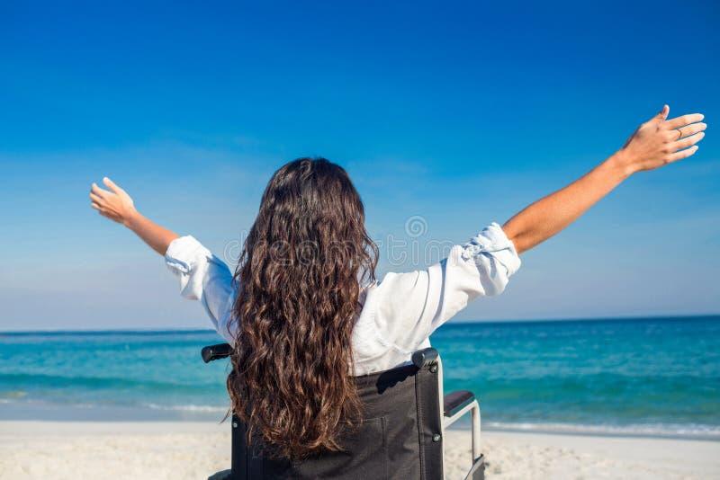 有胳膊的残疾妇女伸出在海滩 免版税库存图片