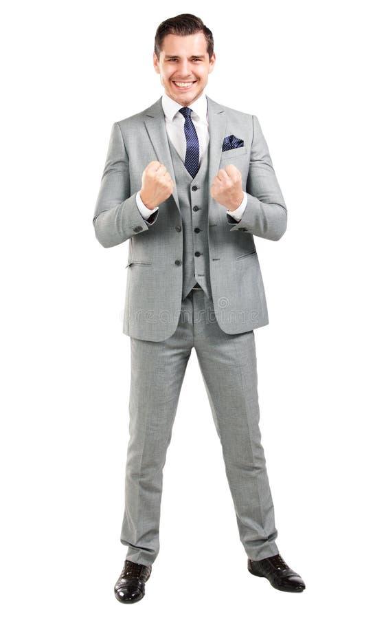 有胳膊的激动的英俊的商人在成功上升了 免版税图库摄影