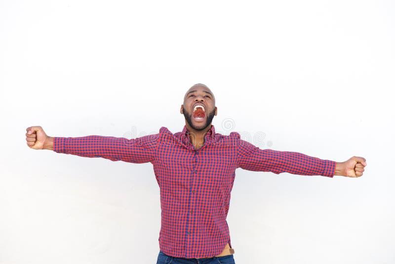 有胳膊的激动的年轻非洲人伸出呼喊 免版税图库摄影