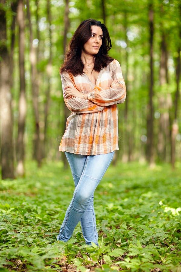 有胳膊的美丽的妇女在森林里折叠了 库存照片