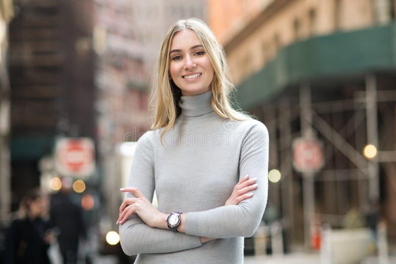 有胳膊的美丽的微笑的女实业家在城市街道上横渡了站立户外 免版税库存照片