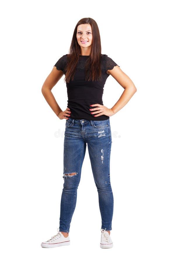 有胳膊的美丽的年轻深色的妇女在她的臀部 免版税库存照片