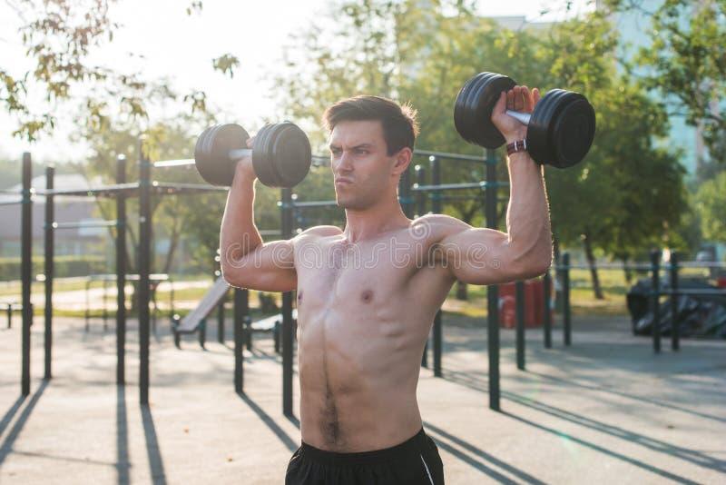 有胳膊的肌肉男性运动员提高了做举的锻炼哑铃 免版税库存图片