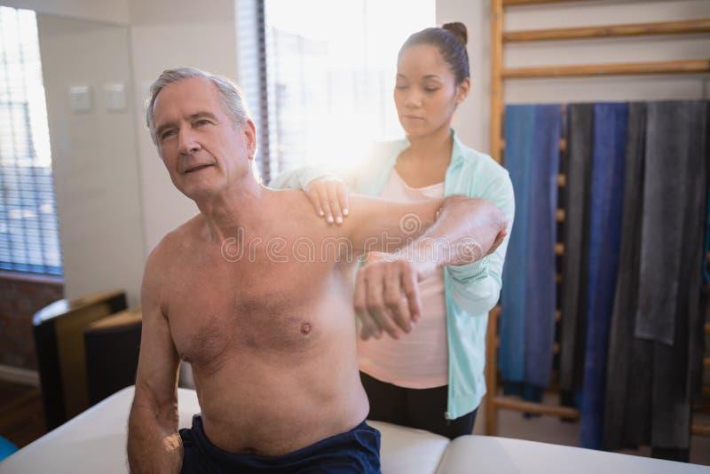 有胳膊的赤裸上身的资深男性患者提高了接受脖子按摩从女性治疗师 库存照片