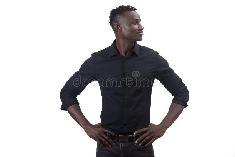 有胳膊的非洲人在看对边的腰部,微笑 免版税图库摄影