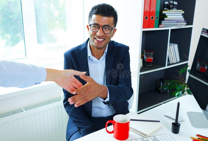 有胳膊的年轻商人延伸到握手 图库摄影
