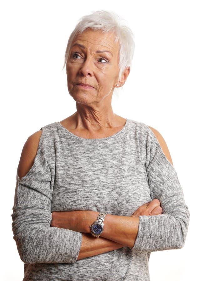 有胳膊被折叠的看的成熟妇女  免版税库存照片