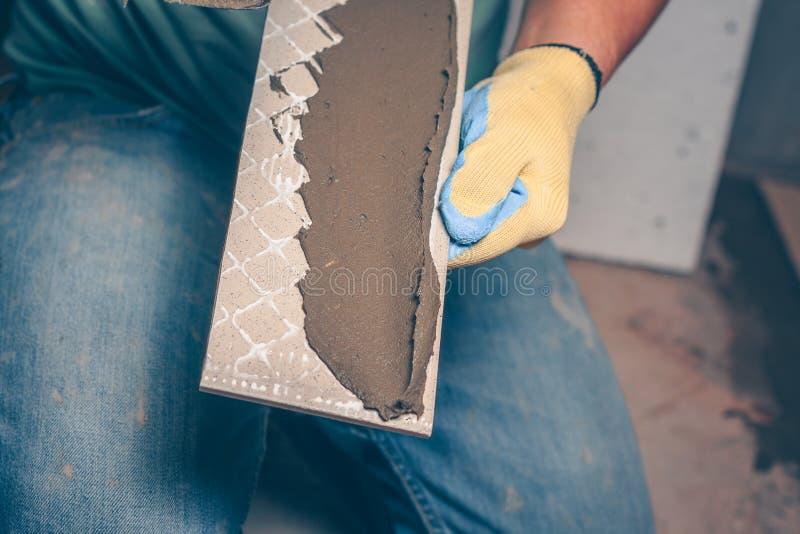 有胶浆的狭窄的瓦片在铺磁砖工的手上 免版税库存图片