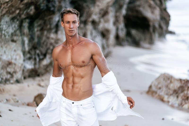有胸部赤裸的性感的肌肉人在白色裤子脱在海滩,在背景的岩石的白色衬衫 库存图片