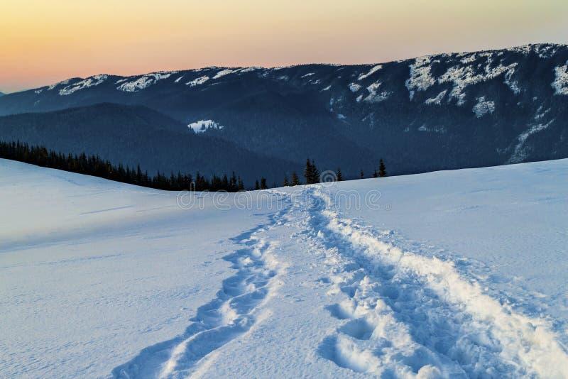 有脚印的道路在冬天山的雪 库存图片