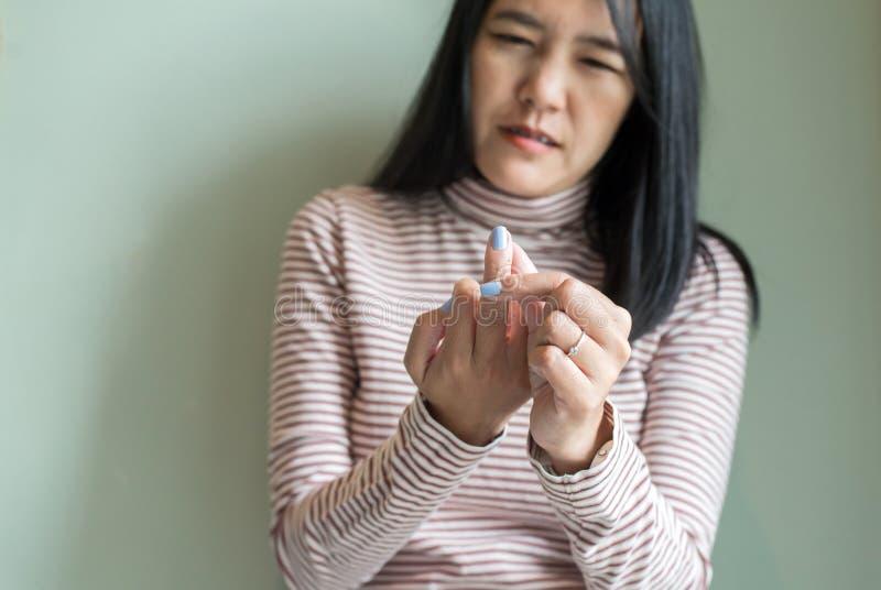 有脚气病在手边或手指的,导致神经的炎症的疾病亚裔妇女 免版税库存图片
