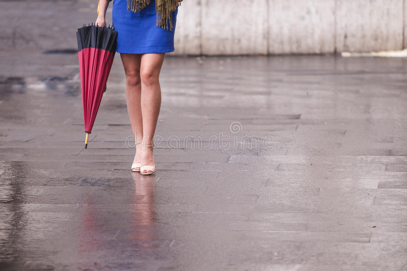 有脚跟和伞的妇女光秃的腿 库存照片